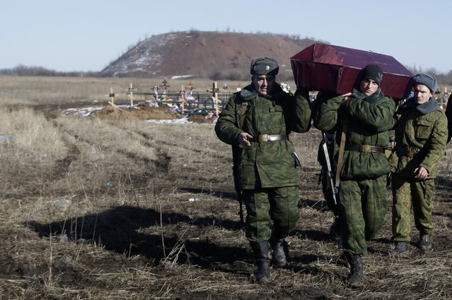 Russia-backed separatists carry a coffin with their comrade during a funeral at a cemetery in the east Ukrainian village of Mospino, near the city of Donetsk, Ukraine, on Thursday, February 12, 2015. (Photo by Petr David Josek/AP Photo)