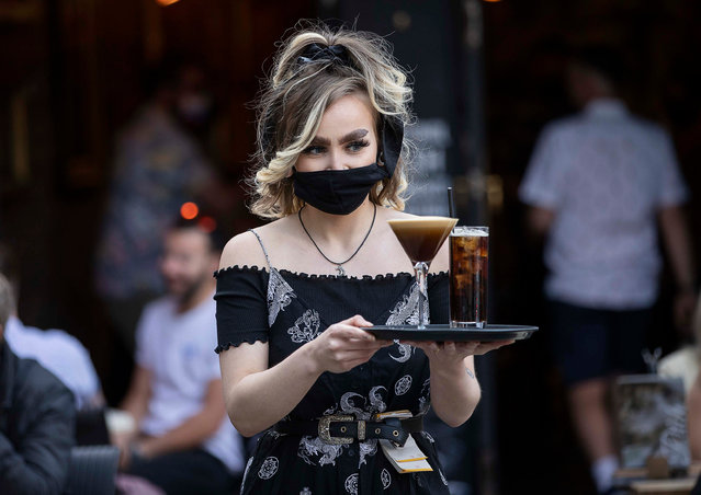 A waitress serves customers in Cardiff, Wales on April 26, 2021 after bars and restaurants re-opened in South Wales as coronavirus restrictions are eased allowing outdoor hospitality to reopen. (Photo by Gareth Everett/Huw Evans/Rex Features/Shutterstock)