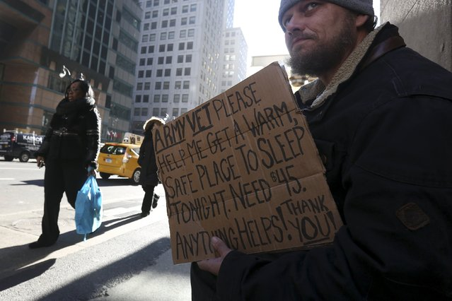 A homeless man sits with a sign on Lexington Avenue in the Manhattan borough of New York, January 4, 2016. New York Governor Andrew Cuomo signed an executive order on Sunday requiring local officials throughout the state to force the homeless into shelters when temperatures dip below freezing and vowed to defend the edict if challenged in court. (Photo by Carlo Allegri/Reuters)