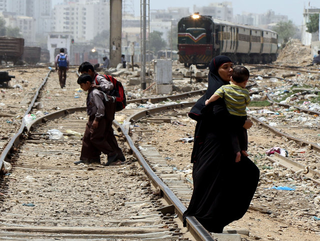 People cross the rail tracks without taking any precautions as a Goods train arrive in Karachi, Pakistan, 29 August 2018. Every year hundreds of people are killed or injured after hitting by trains in Pakistan. (Photo by Rehan Khan/EPA/EFE)