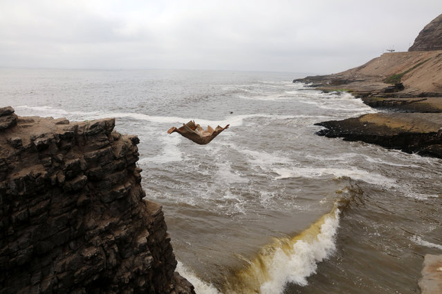 Fernando Jesus Canchari, dressed as a friar  jumps from a 13-meter high cliff along Herradura Beach in Lima, December 7, 2016. (Photo by Guadalupe Pardo/Reuters)