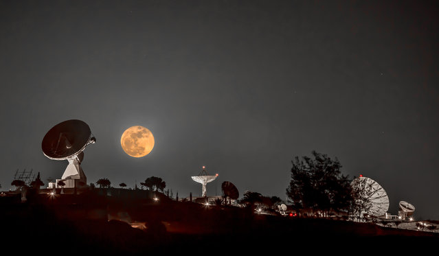 """This gorgeous image shows this month's full Moon, also known as a """"Cold Moon"""", seeming to hover above a set of satellite tracking dishes on the campus of the Instituto Nacional de Tecnica Aerospacial (INTA), in the southern part of the Canary Islands' Gran Canaria, at Montaña Blanca. One of the antennas – the 15 m-diameter dish seen at left – is ESA's Maspalomas tracking station, which currently communicates with ESA's Cluster, LISA Pathfinder and XMM-Newton missions. It was captured on December 14, 2016 by amateur photographer Claus Vogl, from Fürth, Germany. (Photo by Claus W. Vogl)"""