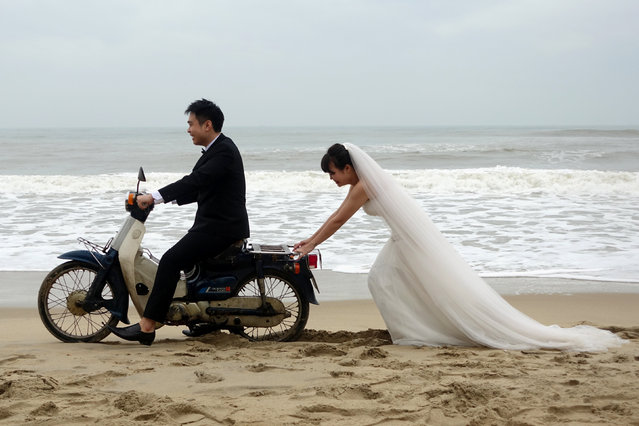 A Vietnamese bride is seen pushing the groom on a scooter during a photo shoot for their wedding in An Bang Beach outside Hoi An in Vietnam December 11, 2016. (Photo by Reuters/Stringer)
