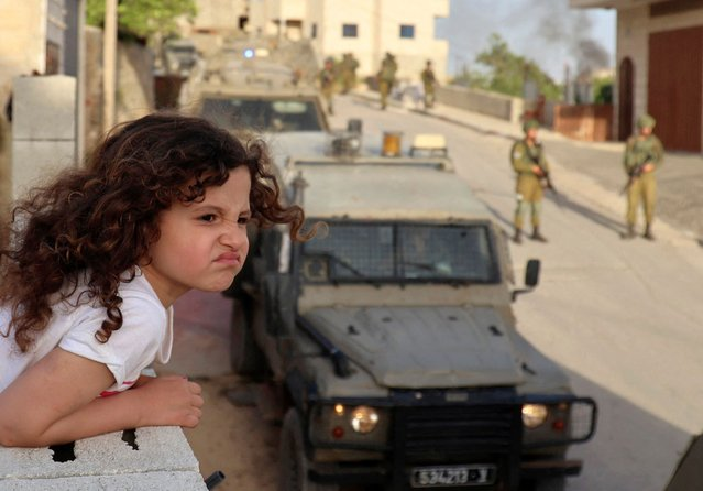 A Palestinian girl watches from the balcony of her house as Israeli soldiers conduct a security operation in the village of Aqraba, east of Nablus in the occupied-West Bank, on May 3, 2021. Suspected Palestinian gunmen carried out a drive-by shooting at a nearby junction the previous, leaving three Israeli civilians wounded, one of them in critical condition, with a manhunt underway. (Photo by Jaafar Ashtiyeh/AFP Photo)