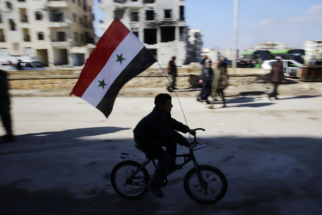 A Syrian boy rides a bike adorned with a Syrian flag as Syrians families, who were displaced from east Aleppo last month, return to their homes in the Hanano district of eastern Aleppo, Syria, Sunday, December 4, 2016. On Nov. 26, government forces stormed the Hanano district, their deepest incursion into east Aleppo in more than four years. Abdul-Ghani Kassa, Aleppo's deputy governor, said some 750 families have so far returned the Hanano, a district subjected to wide destruction during government shelling and airstrikes on the area. (Photo by Hassan Ammar/AP Photo)