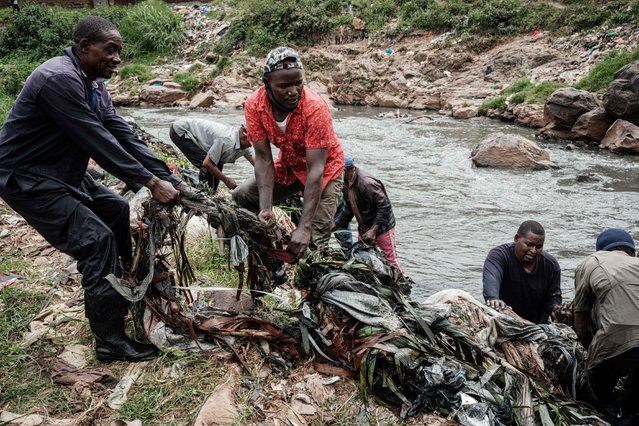 Members of the local voluntary group, the Canaan Riverside Green Peace, remove debris from the Nairobi River after rains at Dandora slum in Nairobi on June 5, 2021, on World Environment Day. Every weekend for the past two years, the group has cleaned the filthy river and planted about five hundred trees to create a forest which filters the smoke from a dumping site nearby. (Photo by Yasuyoshi Chiba/AFP Photo)