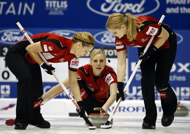 Switzerland's Nadine Lehmann (C) delivers a stone as her teammates Nicole Schwaegli (L) and Marisa Winkelhausen sweep during their curling round robin game against Germany at the World Women's Curling Championships in Sapporo March 15, 2015. (Photo by Thomas Peter/Reuters)