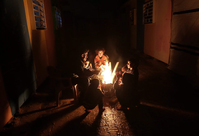 43-year-old Ayman Al-Kfarnih and his family warm up in front of a fire as they endure the cold weather outside their temporary housing, after their house was destroyed during the Israeli war against the Gaza strip in the summer of 2014, Beit Hanoun town, northern Gaza Strip, 26 January 2016. (Photo by Mohammed Saber/EPA)