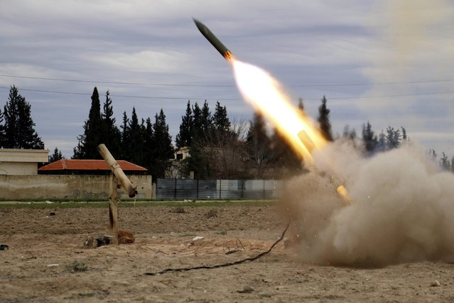 Jaish Al-Islam (Army of Islam) brigade fighters launch a rocket towards forces loyal to Syria's President Bashar Al-Assad located beside Damascus International airport, from the eastern Damascus suburb of Ghouta February 24, 2015. (Photo by Amer Almohibany/Reuters)