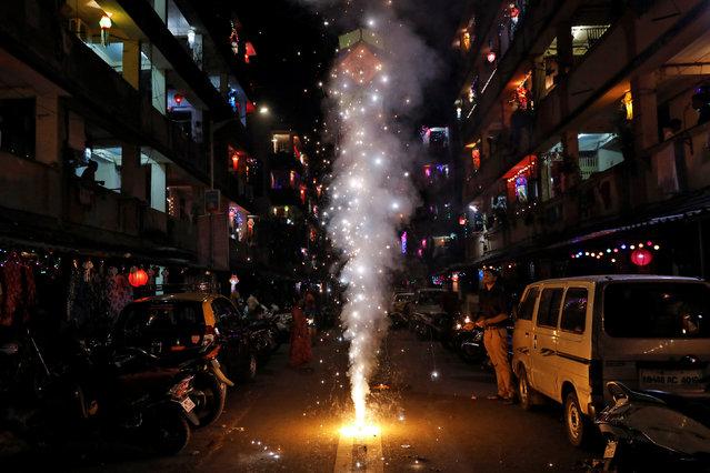 A man lights a firecracker while celebrating Diwali in Mumbai, India on November 7, 2018. (Photo by Danish Siddiqui/Reuters)