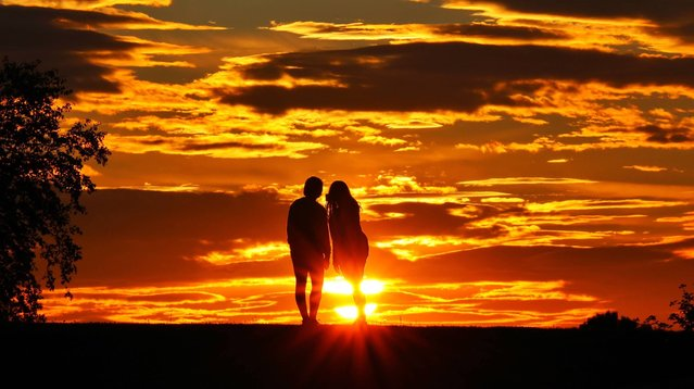 A couple stop and take a moment to view the beautiful sunset in Gateshead, a large town in Tyne and Wear, United Kingdom on June 7, 2021. (Photo by NNP)