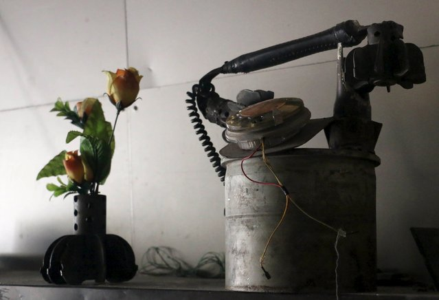 """A makeshift vase and telephone made from remnants of mortar shells are placed inside Abu Khaled's shop in the Douma neighborhood of Damascus April 28, 2015. Abu Khaled opened a shop for making """"barley bread"""" using remnants of weapons including rockets, tank shells and other ordnance fired by forces loyal to Syria's President Bashar al-Assad. (Photo by Amer Almohibany/Reuters)"""