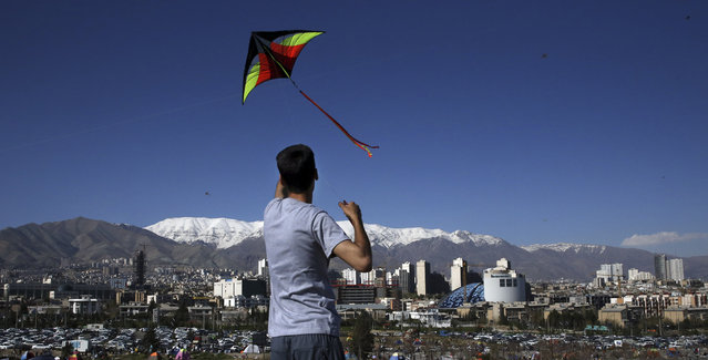 An Iranian man flies a kite during the ancient festival of Sizdeh Bedar, an annual public picnic day on the 13th day of the Iranian new year, at the Pardisan Park in Tehran, Iran, Thursday, April 2, 2015. Iranians flocked to parks and wilderness on Thursday to mark the ancient festival, a legacy from pre-Islamic era, in the last day of Persian New Year holidays. Sizdeh means 13 and Bedar means day out in Persian and it is believed unlucky to stay indoors on Sizdeh Bedar which means getting rid of number 13. (Photo by Vahid Salemi/AP Photo)