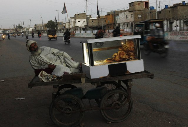 "Najeeb, 70, waits for customers while selling ""bakarkhani"", a traditional snack, at his push cart along a road in Karachi February 16, 2015. (Photo by Akhtar Soomro/Reuters)"