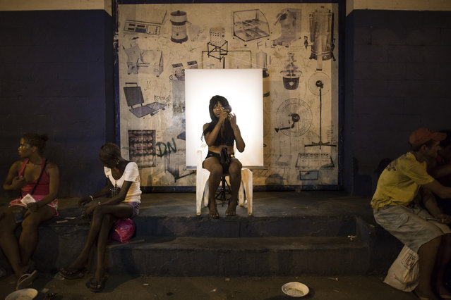 "In this March 14, 2015 photo, Lucilene Gomes, 44, adjusts her hair in preparation for a portrait, poses for a portrait in an open-air crack cocaine market, known as a ""cracolandia"" or crackland where users can buy crack, and smoke it in plain sight, day or night, in Rio de Janeiro, Brazil. Gomes posed in a makeshift studio made up of an old chair against a white backdrop illuminated by two small lights. (Photo by Felipe Dana/AP Photo)"