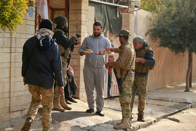 A civilian gives tea to Iraqi rapid response forces during battle with Islamic State militants in the Mithaq district of eastern Mosul, Iraq, January 4, 2017. (Photo by Thaier Al-Sudani/Reuters)