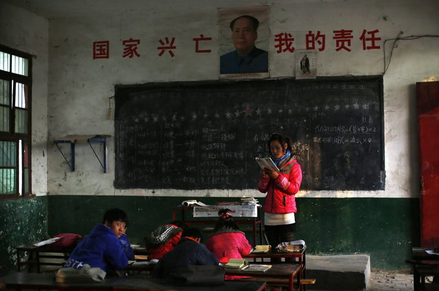 Teacher Xia Jingjing reads a lecture inside a classroom at the Democracy Elementary and Middle School in Sitong town, Henan province December 3, 2013. (Photo by Carlos Barria/Reuters)
