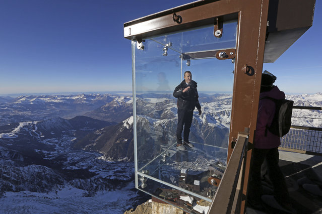 """In this photo taken on Tuesday, December 17, 2013, Mathieu Dechavanne, head of the Compagnie du Mont Blanc which runs the new attraction, stands in a glass cage named """"Pas dans le Vide"""" (Step into the Void) at the top of the Aiguille du Midi peak (3842-meters high or 12,604 feet), in the French Alps, during a press visit. (Photo by Alexis Moro/AP Photo)"""