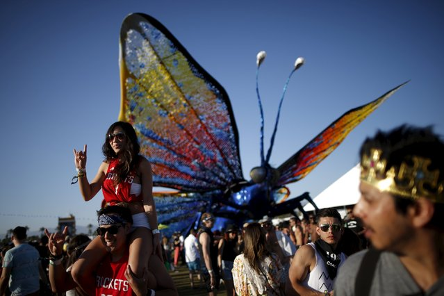 People pose in front of a butterfly artwork at the Coachella Valley Music and Arts Festival in Indio, California April 12, 2015. (Photo by Lucy Nicholson/Reuters)