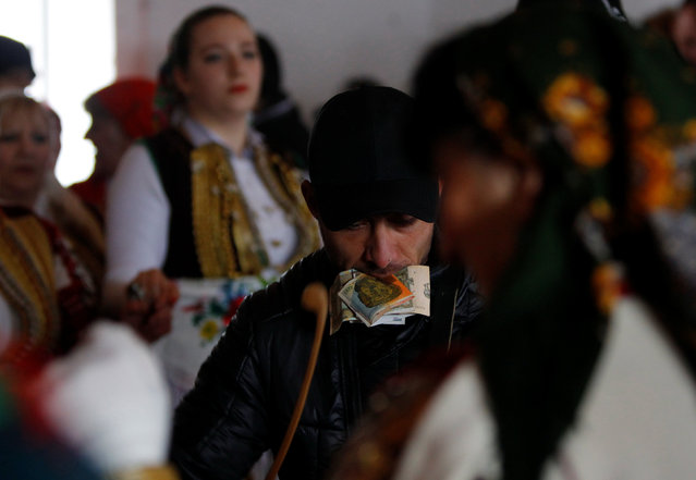 A musician holds banknotes in his mouth as he performs during the Epiphany day celebration in Bitushe, Macedonia January 19, 2017. (Photo by Ognen Teofilovski/Reuters)