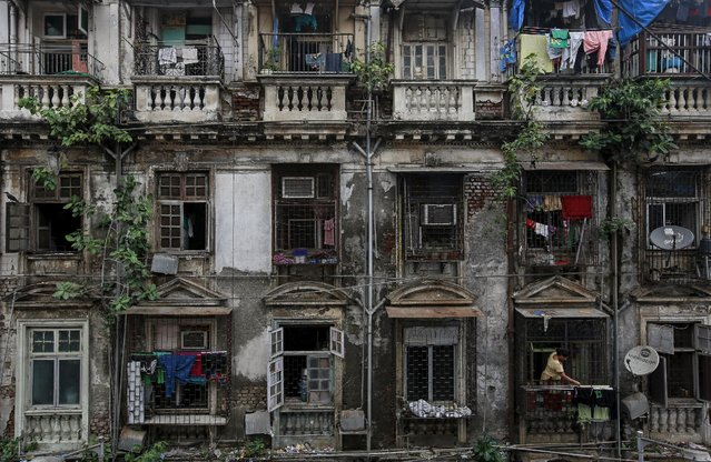 A woman hangs clothes outside the window of an apartment of an old residential building in Mumbai October 1, 2014. The cost for buying 450 square feet (41 square meters) one-room apartment in this building is around 15,555 Indian rupees ($ 250) per square feet or 7,000,000 Indian rupees ($ 112,000). The rent for an apartment in the same building is around 15,000 Indian rupees ($ 240) per month. (Photo by Danish Siddiqui/Reuters)