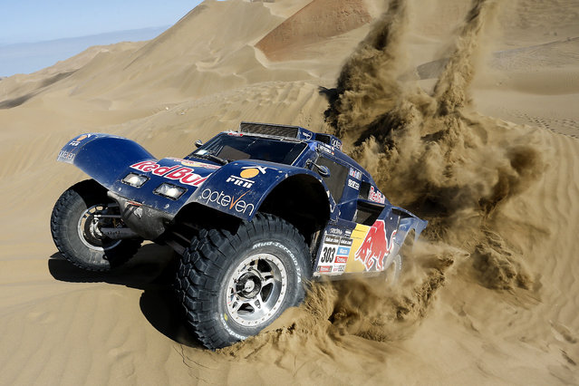 Carlos Sainz of Spain and co-pilot Timo Gottschalk of Germany drive their buggy through the dunes during the tenth stage of the Dakar Rally between the cities of Iquique and Antofagasta, Chile, on January 15, 2014. (Photo by Victor R. Caivano/Associated Press)