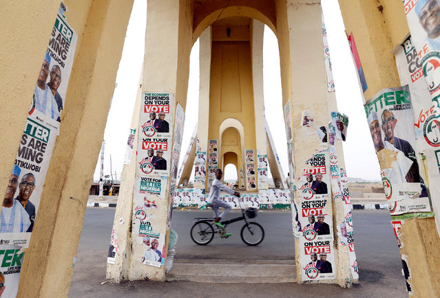 A boy rides a bicycle past a monument decorated with election posters depicting Nigeria's main opposition party presidential candidate Atiku Abubakar with his running mate, Peter Obi, in Yola, Adamawa State, Nigeria  February 26, 2019. (Photo by Nyancho NwaNri/Reuters)