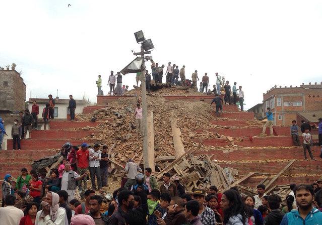 People stand around damage caused by an earthquake at Durbar Square in Kathmandu, Nepal, Saturday, April 25, 2015. (Photo by Niranjan Shrestha/AP Photo)