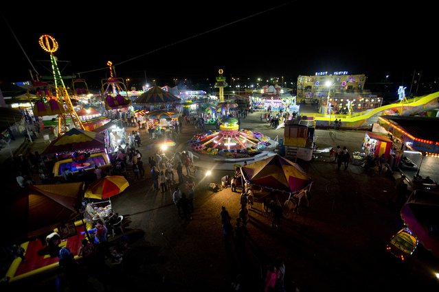In this April 11, 2015 photo, rides are illuminated at the Texcoco Fair on the outskirts of Mexico City. Although it began as a celebration of horses, it now resembles many county or state fairs in Mexico and even the United States, with its game booths, food, beer and musical performances. (Photo by Eduardo Verdugo/AP Photo)