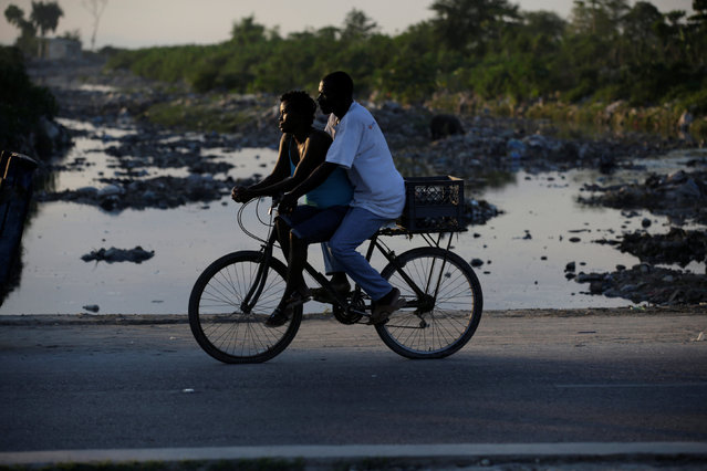 A woman and a man ride a bicycle along a street in Port-au-Prince, Haiti, December 1, 2016. (Photo by Andres Martinez Casares/Reuters)