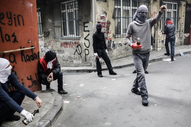 Protestors hold molotov cocktails during a May Day rally near Taksim Square in Istanbul on May 1, 2015. Turkish police put Istanbul under a security shutdown to thwart unauthorised demonstrations on a tense May Day, as tens of thousands of labour activists turned out worldwide to defend their rights at a time of austerity. (Photo by Yasin Akgul/AFP Photo)