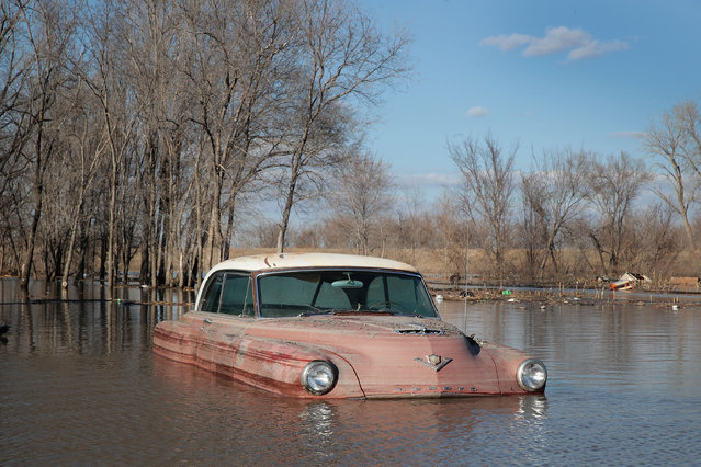 "A vintage car sits in flood water on March 20, 2019 in Hamburg, Iowa. Although flood water in the town has started to recede many homes and businesses remain surrounded by water. Several Midwest states are battling some of the worst flooding they have experienced in decades as rain and snow melt from the recent ""bomb cyclone"" has inundated rivers and streams. At least three deaths have been linked to the flooding. (Photo by Scott Olson/Getty Images)"