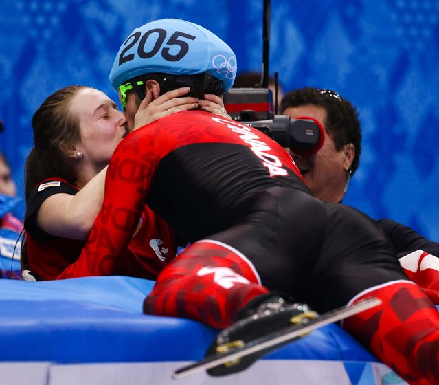 Charles Hamelin of Canada, right, embraces Marianne St. Gelais after he won the men's 1500m short track speed skating final at the Iceberg Skating Palace during the 2014 Winter Olympics, on February 10, 2014. (Photo by Darron Cummings/Associated Press)