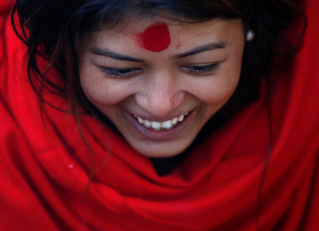 A devotee smiles as she offers prayers during the Swasthani Brata Katha festival in Kathmandu, Nepal January 12, 2017. (Photo by Navesh Chitrakar/Reuters)