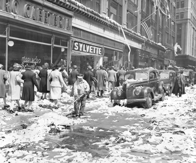 A Lone Street Cleaner Pushes His Broom In An Uphill Battle to Clean away the paper tossed by joyous New Yorkers in Celebration of the end of the war on May 7. The Scene is at 36th street and Sixth Avenue, New York City. May 07, 1945. (Photo by New York Post/Photo Archives, LLC via Getty Images)