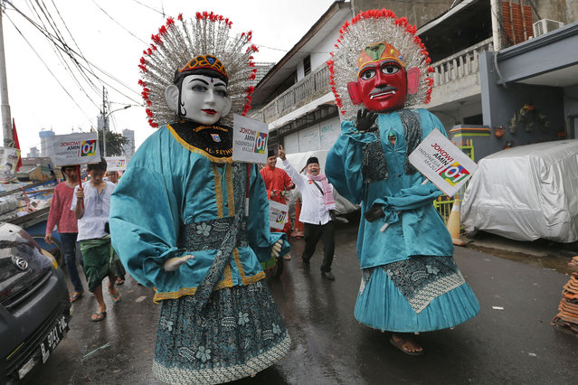 """Dancers in traditional giant puppets called """"ondel-ondel"""" perform during a campaign rally for legislative candidates in Jakarta, Indonesia, Friday, April 12, 2019. Indonesia is gearing up to hold its presidential election on April 17 which will pit Indonesian President Joko Widodo against his challenger, former special forces general Prabowo Subianto. (Photo by Tatan Syuflana/AP Photo)"""
