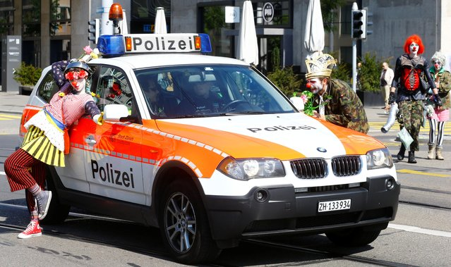 Protesters dressed as clowns pose beside a Swiss police car during a May Day demonstration in Zurich, Switzerland on May 1, 2019. (Photo by Arnd Wiegmann/Reuters)