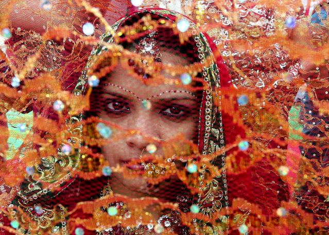 A bride takes part in a mass marriage ceremony in Bhopal, India, 24 February 2014. Some 45 bridal pairs married during the wedding ceremony organised for underprivileged couples under Mukhyamantri Kanyadan Yojna (Chief Minister Welfare Scheme). Some communities undertake the responsibility of arranging mass marriages for the couples who are financially unsound. (Photo by Sajneev Gupta/EPA)