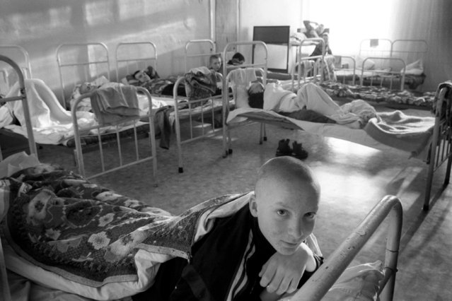 Street children at the Maikovska state centre in Kiev await the end of their afternoon nap, 2002. The ill-equipped centre was set up to aid homeless children in making the transition from the streets to society but for many children the centre is a temporary and unwanted respite from Kiev's city streets. Many children on the street fear the centre, as tales of abuse from the poorly trained and underpaid staff are widespread. For many former communist countries, the painful transition to a free market economy is evident in the escalating number of homeless children. In Ukraine, a staggering 10% of the population consists of abandoned children. Many of these 800,000 children face abuse by the system, the mafia and each other. (Photo by Kurt Vinion /Getty Images)