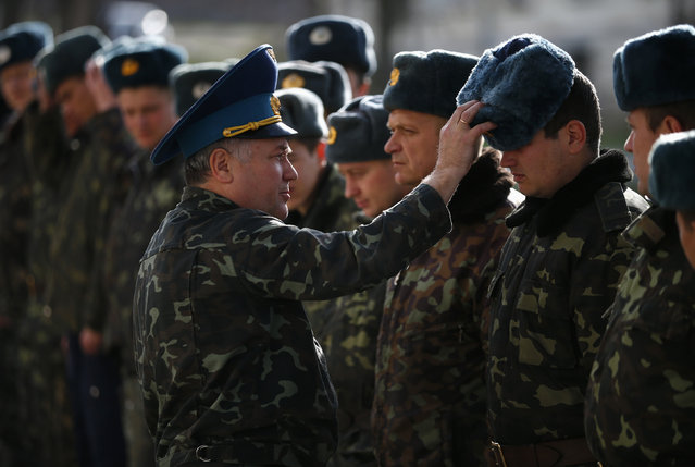 Viktor Kukharenko, chief of staff of a base in the Crimean village of Belbek, adjusts the hat of a soldier in the base, near Simferopol March 6, 2014. (Photo by Thomas Peter/Reuters)