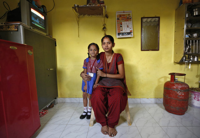 Sulochna Mohan Sawant, 23, poses with her five-year-old daughter Shamika Sawant inside their home in Mumbai February 13, 2014. Sulochna, who works as a maid, wanted to become a doctor when she was a child. However, she could only study until the age of 14. Sulochna wants her daughter to become a teacher, Shamika also wants to become a teacher. (Photo by Mansi Thapliyal/Reuters)
