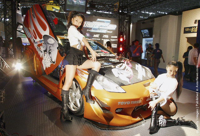 Models display a car to promote the game Need For Speed Underground 2