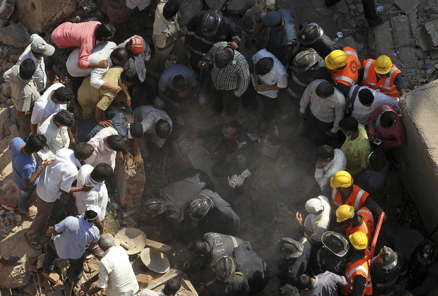Rescue workers search for survivors in the debris of a building that collapsed in Mumbai, India, Friday, March 14, 2014. A seven-story residential building collapsed Friday in a Mumbai suburb and up to 10 people may be trapped under the debris, Indian officials said. (Photo by Rafiq Maqbool/AP Photo)