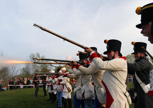 People dressed as Austrian soldiers of the Habsburg dynasty fire their rifles during the re-enactment of the battle agains Hungarian Hussars in Tapiobicske, Hungary  April 4, 2016. (Photo by Laszlo Balogh/Reuters)