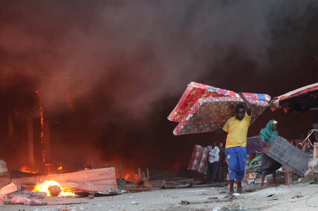 Somali traders salvage some of their wares from the burning stalls at the main Bakara market in Somalia's capital Mogadishu, February 27, 2017. (Photo by Ismail Taxta/Reuters)