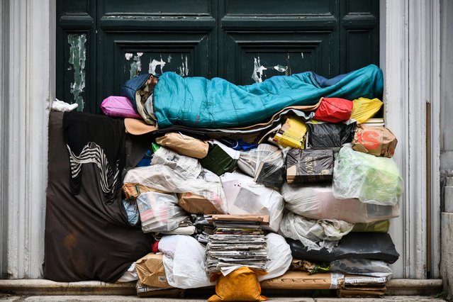 A homeless man sleeps on a pile of plastic bags and newspapers under a porch on April 7, 2019 in Rome, Italy. (Photo by Vincenzo Pinto/AFP Photo)