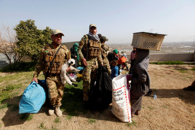 Members of the rapid response forces help displaced people, who fled their home, as they look for safe area in Mosul, Iraq February 28, 2017. (Photo by Alaa Al-Marjani/Reuters)