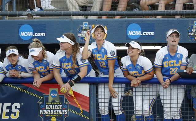 The UCLA dugout celebrates in the sixth inning of the first game of the best-of-three championship series against Oklahoma in the NCAA softball Women's College World Series in Oklahoma City, Monday, June 3, 2019. (Photo by Alonzo Adams/AP Photo)