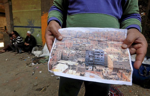 """A man, whose job is sorting out garbage, shows a photo of houses in Zaraeeb, with outlined plans for a mural by French-Tunisian artist El Seed, in the shanty area known as Zabaleen or """"Garbage City"""" on the Mokattam Hills in eastern Cairo, Egypt, April 4, 2016. (Photo by Amr Abdallah Dalsh/Reuters)"""