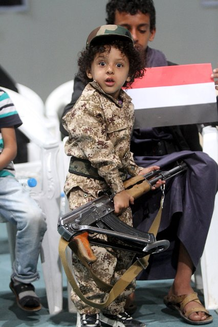 A boy looks on while holding a rifle and attending celebrations with his brother marking the 25th anniversary of Yemen's unification in Sanaa May 23, 2015. (Photo by Mohamed al-Sayaghi/Reuters)